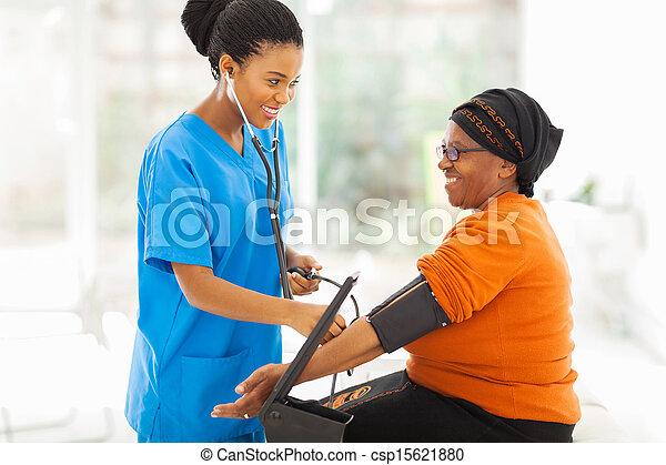 Afrikanische Krankenschwester überprüft den Blutdruck eines Senior Patienten - csp15621880