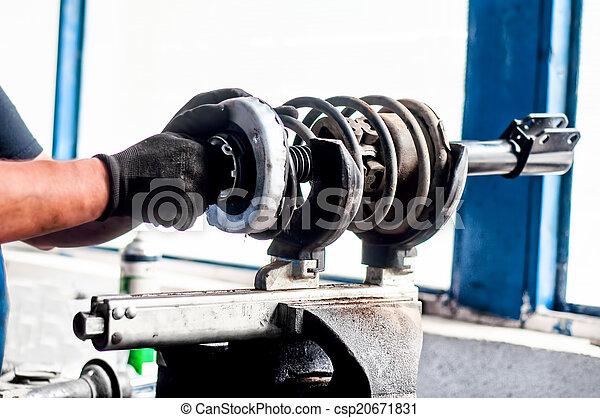 Automechaniker, der einen Auto-Dämpfer im Auto anpasst. - csp20671831