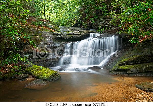 Bewegung verschwommene Wasserfälle, friedliche Naturlandschaft in den blauen Bergkammbergen mit üppigen grünen Bäumen, Felsen und fließendem Wasser - csp10775734