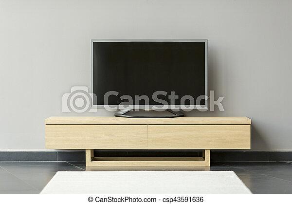 Flat-TV steht auf dem Kommode im Raum. - csp43591636