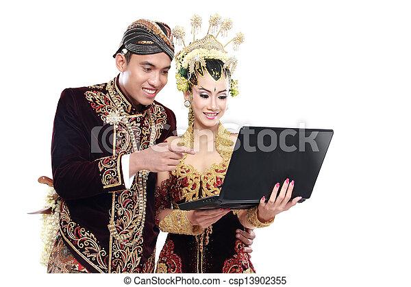 Frohes traditionelles japanisches Hochzeitspaar mit Laptop - csp13902355