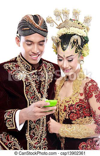 Frohes traditionelles Java-Hochzeitspaar mit Handy - csp13902361