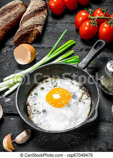 Gebratenes Ei in einer Pfanne mit Brot und Tomaten. - csp67049479