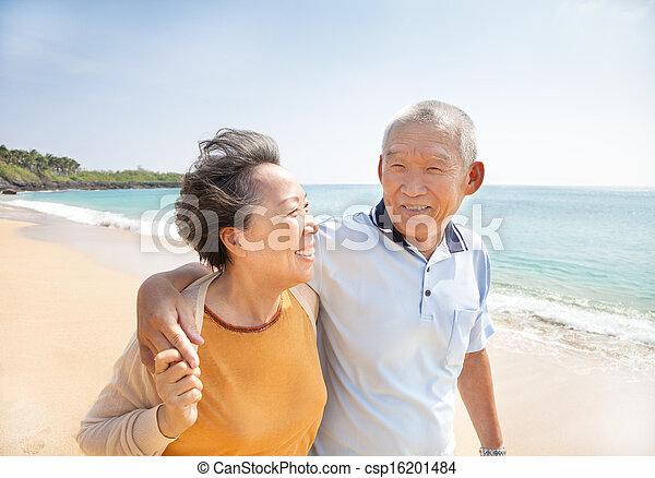 Glückliche Abschlussschüler, die am Strand spazieren gehen - csp16201484