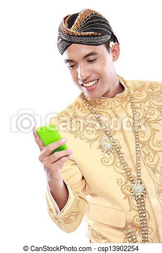 Mann mit traditionellem Java-Anzug mit Handy - csp13902254