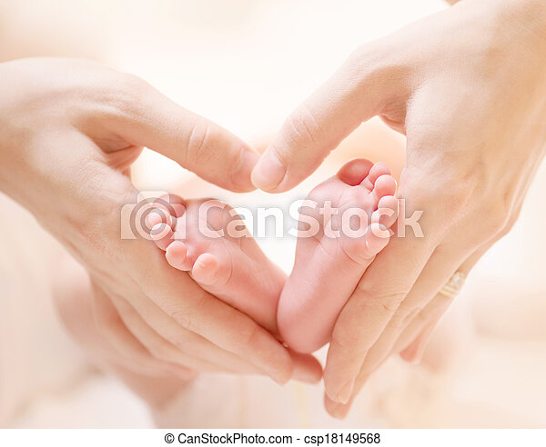 Kleine Neugeborene Füße auf weiblichen Herzen formten sich die Hände. - csp18149568