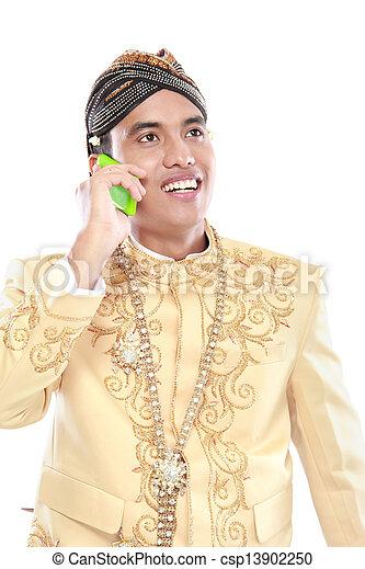 Mann mit traditionellem Java-Anzug mit Handy - csp13902250