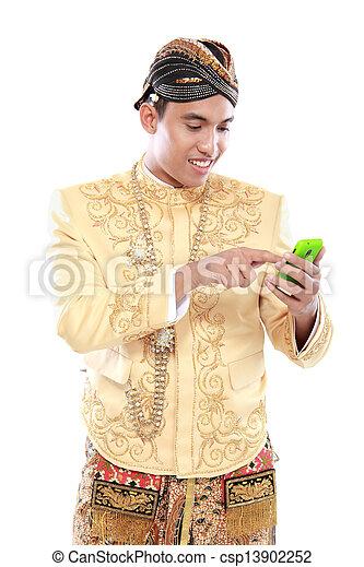 Mann mit traditionellem Java-Anzug mit Handy - csp13902252