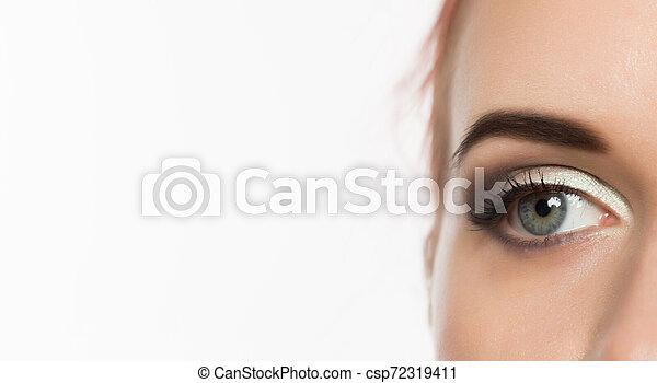 Nahes graues Auge mit professionellem Make-up auf der Seite, auf weißem Hintergrund. Freier Raum für Text - csp72319411