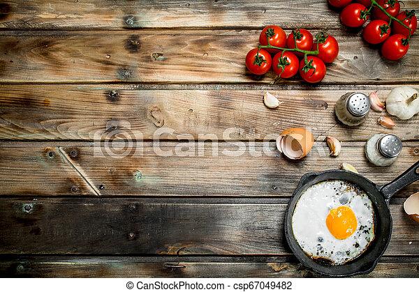 Spiegelei in einer Pfanne mit Tomaten. - csp67049482