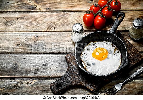 Spiegelei in einer Pfanne mit Tomaten. - csp67049463