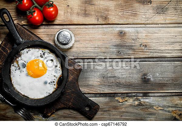 Spiegelei in einer Pfanne mit Tomaten. - csp67146792