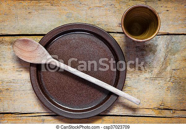 Mittelalterliche Töpfergerichte und Löffel auf einem alten Holztisch - csp37023709