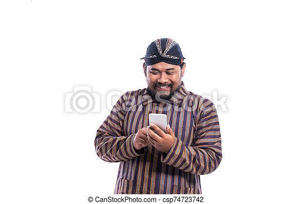 traditionelle , javanese, lurik, mann, tuch, smartphone, gebrauchend - csp74723742